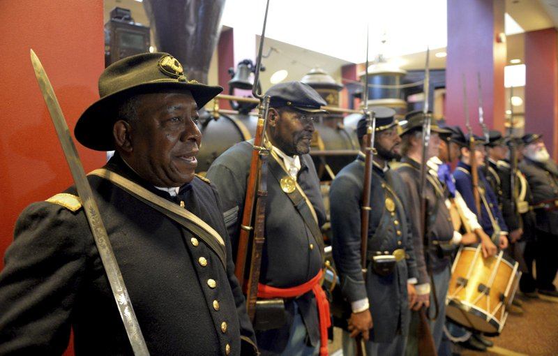 FILE - In this June 20, 2014, file photo, Civil War re-enactors Lt. James Hayes, from left, Samuel Stephenson and Marvin-Alonzo Greer participate in a Juneteenth celebration at the Atlanta Cyclorama and Civil War Museum in Atlanta.  Juneteenth celebration started with the freed slaves of Galveston, Texas. Although the Emancipation Proclamation freed the slaves in the South in 1863, it could not be enforced in many places until after the end of the Civil War in 1865.  (Kent D. Johnson/Atlanta Journal-Constitution via AP, File)