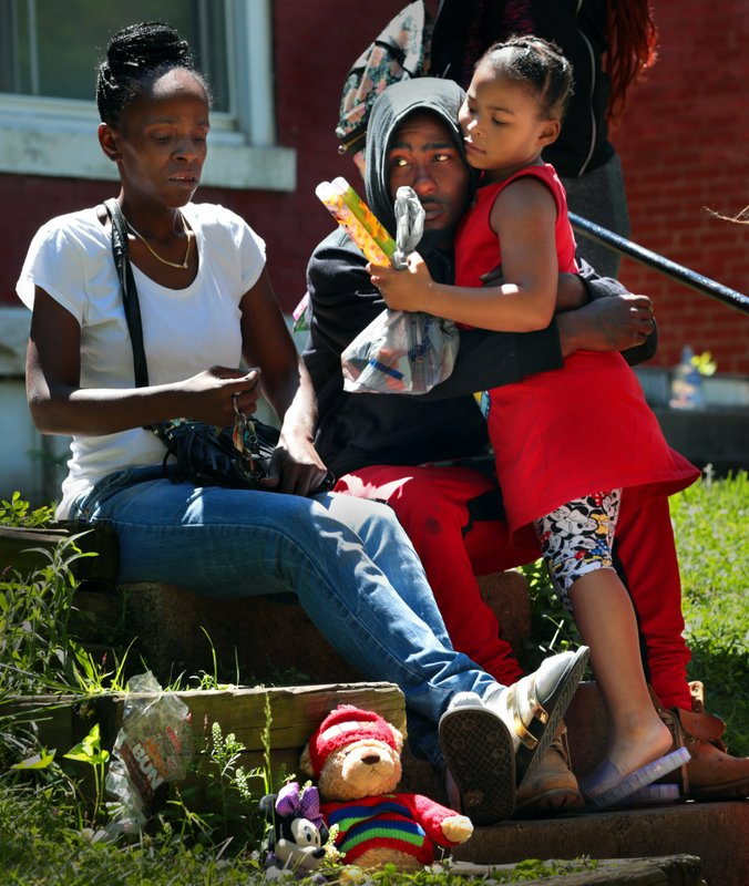 In this Monday, June 10, 2019 photo, Devation Powell, the father of slain 3-year-old Kennedi Powell, hugs his cousin Shylar Roberts, 5, as he sits near where Kennedi was shot the night before along Michigan Avenue in the Mount Pleasant neighborhood of St. Louis. Sharonda Edmondson, Kennedi's great-aunt, is at left. (Robert Cohen/St. Louis Post-Dispatch via AP)