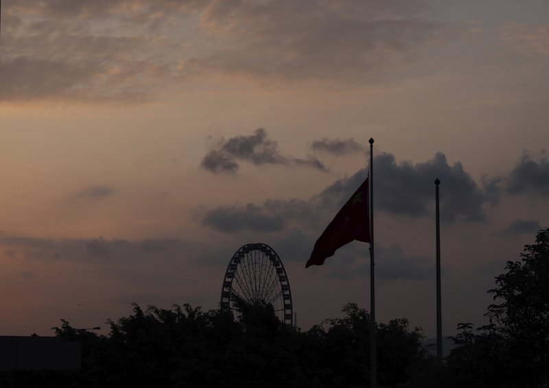 The Chinese national flag is lowered as the sun sets in Hong Kong on Saturday, June 15, 2019. Hong Kong's Chief Executive Carrie Lam said she will suspend a proposed extradition bill indefinitely in response to widespread public unhappiness over the measure, which would enable authorities to send some suspects to stand trial in mainland courts. (AP Photo/Vincent Yu)