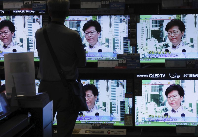 A man watches a broadcast of Chief Executive Carrie Lam speaking at a press conference held in Hong Kong on Saturday, June 15, 2019. Lam said she will suspend a proposed extradition bill indefinitely in response to widespread public unhappiness over the measure, which would enable authorities to send some suspects to stand trial in mainland courts. (AP Photo/Vincent Yu)