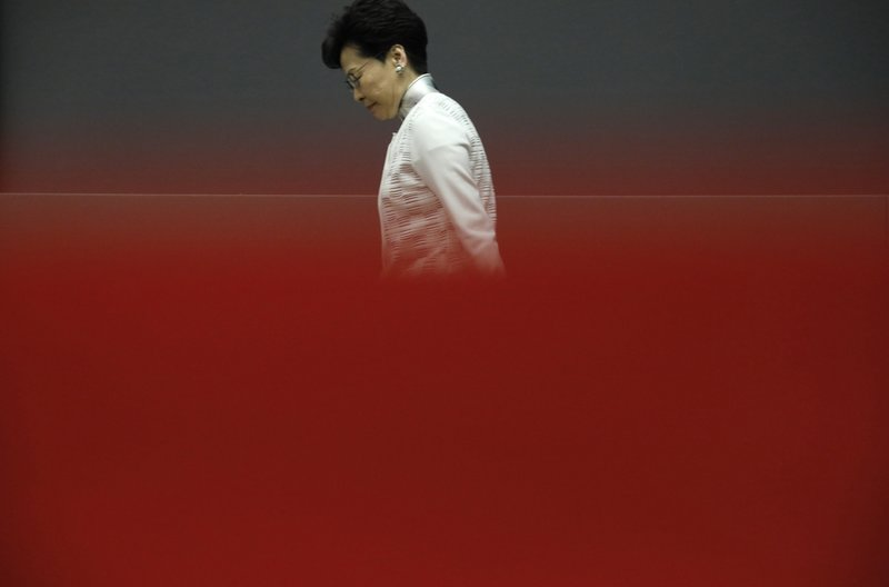 Hong Kong Chief Executive Carrie Lam walks behind a red barrier tape toward a press conference in Hong Kong Saturday, June 15, 2019. Hong Kong Chief Executive Carrie Lam said she will suspend a proposed extradition bill indefinitely. Lam told media Saturday she took the move in response to widespread public unhappiness over the measure, which would enable authorities to send some suspects to stand trial in mainland courts. (AP Photo/Vincent Yu)