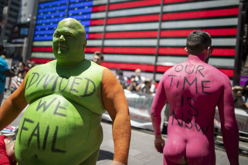 Participants in a Protest Against Divisiveness sponsored by Human Connection Arts assemble before a march in New York's Time Square on Saturday, June 15, 2019. Several dozen people stripped naked and had their bodies painted in midtown Manhattan as part of what was billed as a protest against