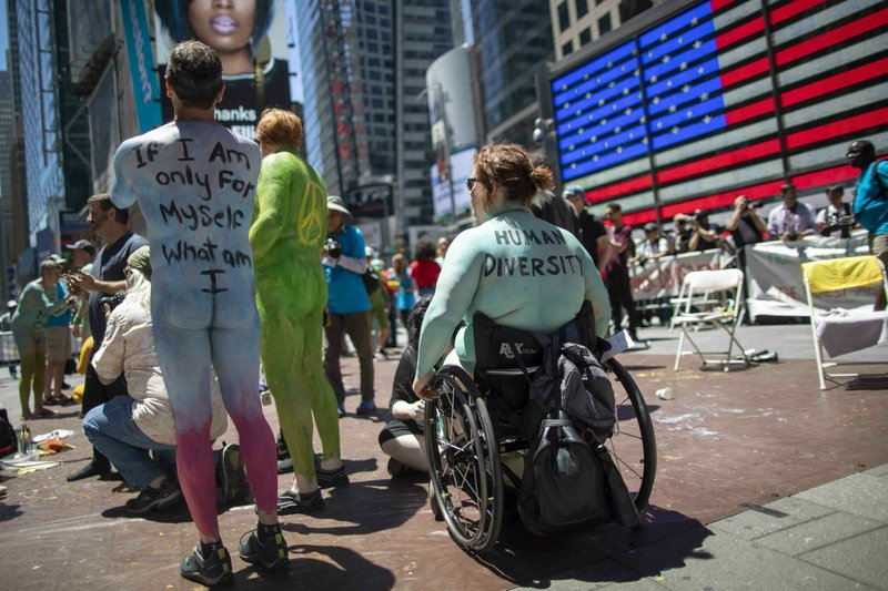 Samantha Walsh, right, of Toronto, prepares to participate in a Protest Against Divisiveness sponsored by Human Connection Arts in New York's Time Square on Saturday, June 15, 2019. Several dozen people stripped naked and had their bodies painted in midtown Manhattan as part of what was billed as a protest against