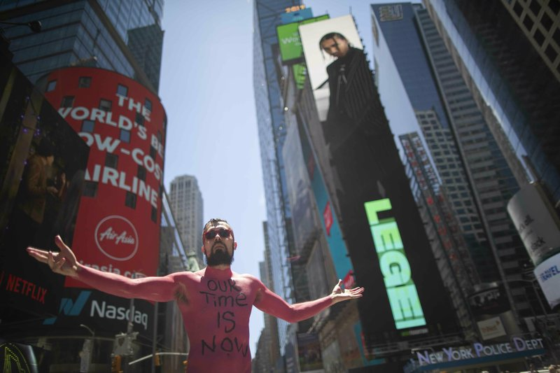 A participant poses for a photo before marching in a Protest Against Divisiveness sponsored by Human Connection Arts in New York's Time Square on Saturday, June 15, 2019. Several dozen people stripped naked and had their bodies painted in midtown Manhattan as part of what was billed as a protest against