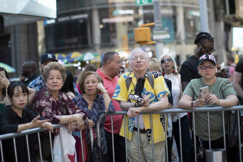 People watch as participants prepare to march during a Protest Against Divisiveness sponsored by Human Connection Arts in New York's Time Square on Saturday, June 15, 2019. Several dozen people stripped naked and had their bodies painted in midtown Manhattan as part of what was billed as a protest against