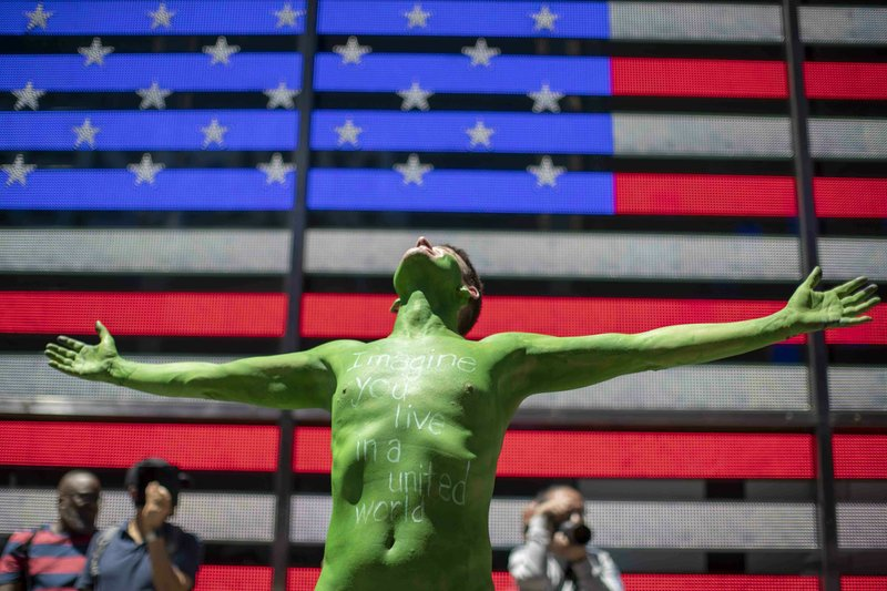 A participant reacts as he prepares to march during a Protest Against Divisiveness sponsored by Human Connection Arts in New York's Time Square on Saturday, June 15, 2019. Several dozen people stripped naked and had their bodies painted in midtown Manhattan as part of what was billed as a protest against