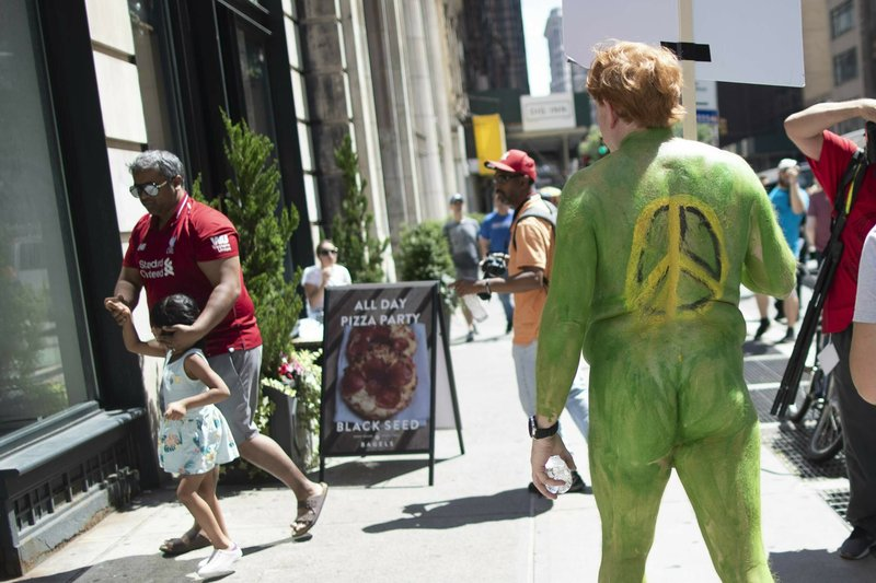 A man shields the eyes of a child as he walk past a participant marching down Broadway during a Protest Against Divisiveness sponsored by Human Connection Arts in New York's Time Square on Saturday, June 15, 2019. Several dozen people stripped naked and had their bodies painted in midtown Manhattan as part of what was billed as a protest against