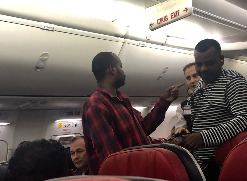 The scene observed by Associated Press photographer Hussein Malla, as an unidentified passenger confronts plane crew members aboard a Turkish Airlines jetliner while in flight from Istanbul, Turkey, Friday June 14, 2019.  The unidentified man had to be subdued when he began smashing at an oxygen mask box and damaged a cabin window, before pushing flight attendants aside and rushing toward the cockpit, but then calmed down and after about 2½ hours flying, the pilots announced that the plane was returning to Istanbul.(AP Photo/Hussein Malla)