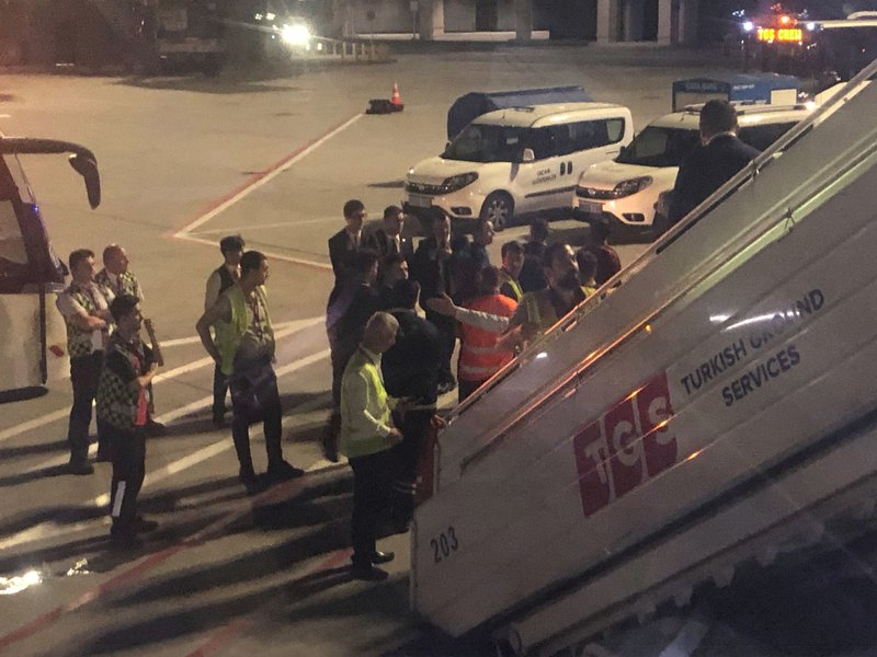 The scene observed by Associated Press photographer Hussein Malla as security, police and and officials remove a passenger from a Turkish Airlines jetliner after the passenger was subdued by passengers and crew following takeoff from Istanbul, Turkey, Friday June 14, 2019.  The unidentified man began smashing at an oxygen mask box and damaged a cabin window, before pushing flight attendants aside and rushing toward the cockpit, but then he calmed down and after about 2½ hours flying, the pilots announced that the plane would return to Istanbul.(AP Photo/Hussein Malla)