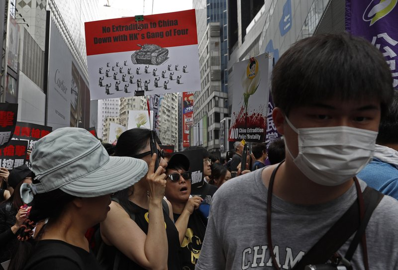 Protesters carrying placards march through the streets against an extradition bill on Sunday, June 16, 2019, in Hong Kong. Tens of thousands of Hong Kong residents, mostly in black, have jammed the city's streets Sunday to protest the government's handling of a proposed extradition bill. (AP Photo/Vincent Yu)