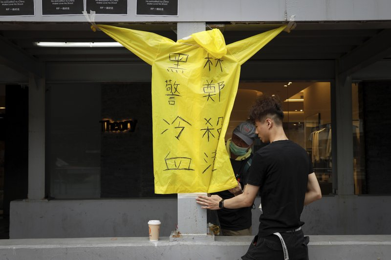 Protesters place a raincoat bearing the words