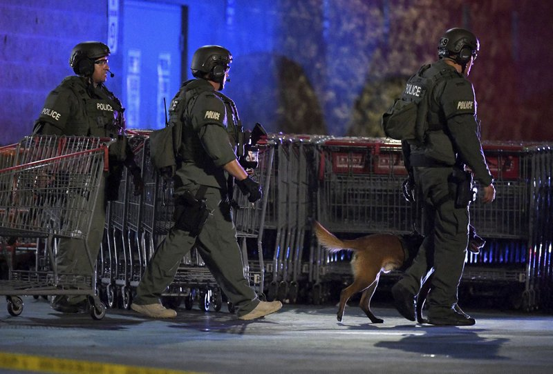 Heavily armed police officers exit the Corona Costco following a shooting inside the wholesale warehouse in Corona, Calif.,  Friday, June 14, 2019.  A gunman opened fire inside the store during an argument,  killing a man, wounding two other people and sparking a stampede of terrified shoppers before he was taken into custody, police said. The man involved in the argument was killed and two other people were wounded, Corona police Lt. Jeff Edwards said.  (Will Lester/Inland Valley Daily Bulletin/SCNG via AP)