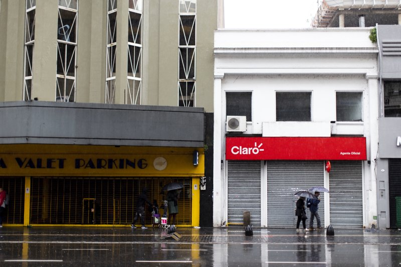 People walk in front of closed stores during a blackout, in Buenos Aires, Argentina, Sunday, June 16, 2019. Argentina and Uruguay were working frantically to return power on Sunday, after a massive power failure left large swaths of the South American countries in the dark. (AP Photo/Tomas F. Cuesta)