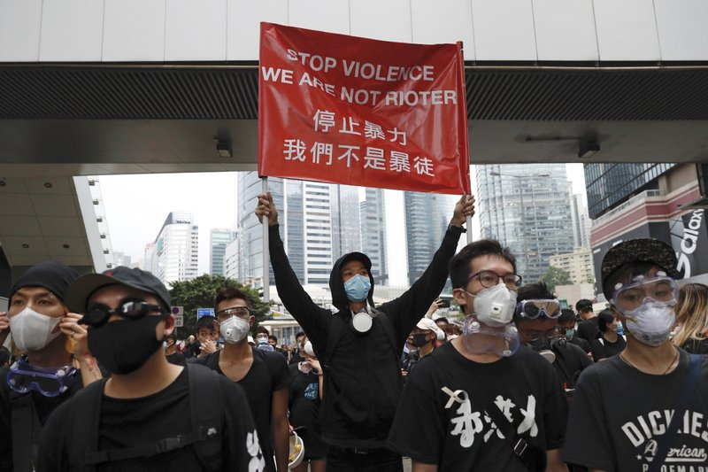 Protesters hold a banner during a march toward the Legislative Council as they continue to protest against the extradition bill in Hong Kong, Monday, June 17, 2019. Hong Kong police announced that they want to clear the streets of protesters Monday morning. Soon after, police lined up several officers deep and faced off against several hundred demonstrators on a street in central Hong Kong. (AP Photo/Vincent Yu)