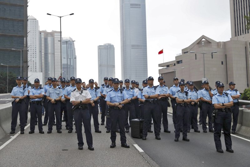 Policemen stand guard on a road as protesters march toward the Legislative Council after they continue to protest against the extradition bill in Hong Kong, Monday, June 17, 2019. Hong Kong police announced that they want to clear the streets of protesters Monday morning. Soon after, police lined up several officers deep and faced off against several hundred demonstrators on a street in central Hong Kong. (AP Photo/Vincent Yu)