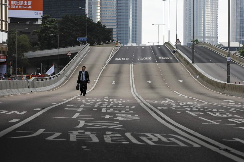 A man walks alone on a empty road near the Legislative Council after protesters continue to protest against the extradition bill in Hong Kong, Monday, June 17, 2019. Hong Kong police announced that they want to clear the streets of protesters Monday morning. Soon after, police lined up several officers deep and faced off against several hundred demonstrators on a street in central Hong Kong. (AP Photo/Vincent Yu)