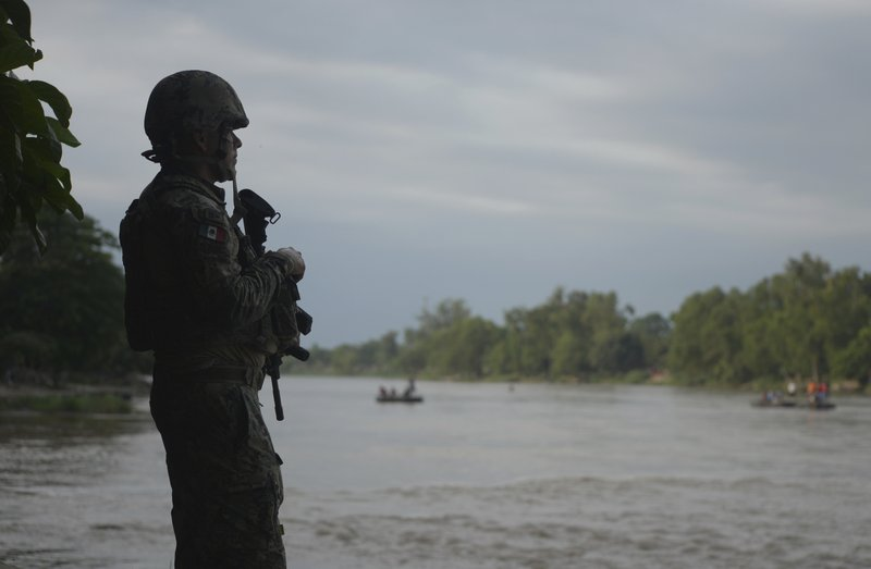 A Mexican marine stands guard on the Suchiate River, watching out for migrants crossing from Guatemala to Ciudad Hidalgo, Mexico, Sunday, June 16, 2019. Mexico faces heightened pressure from the U.S. to reduce the surge of mostly Central American migrants through its territory. (AP Photo/Idalia Rie)