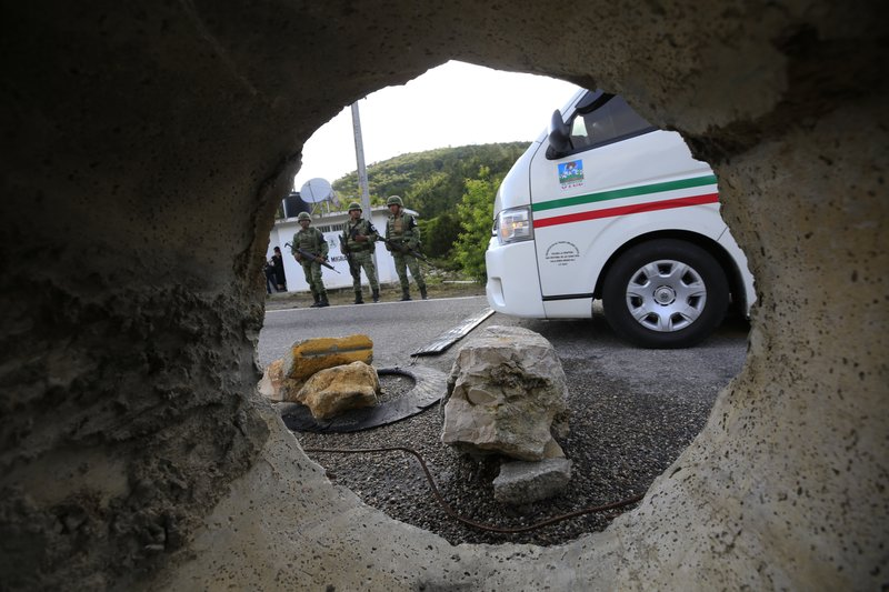 Seen through a section of pipe placed the middle of a road between two-way traffic, soldiers forming part of the National Guard stand guard at an immigration checkpoint heading north out of Comitan, Chiapas state, Mexico, Sunday, June 16, 2019. Mexican President Andrés Manuel López Obrador said Saturday his country must help Central Americans fleeing poverty and violence, even as it increases security and revisions to deter migrants from passing through Mexico on route to the U.S. (AP Photo/Rebecca Blackwell)