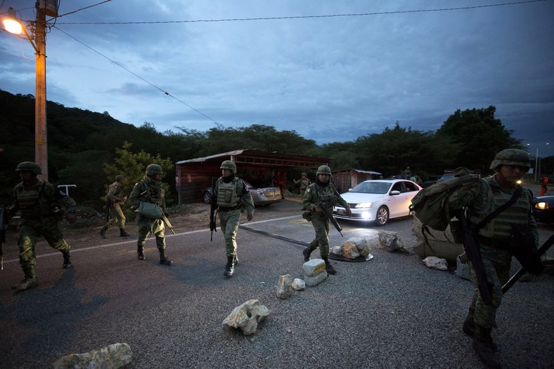 Soldiers wearing the armbands of Mexico's National Guard walk at a migration checkpoint on the highway north of Comitan, Chiapas State, Mexico, Saturday, June 15, 2019. Under pressure from the U.S. to slow the flow of migrants north, Mexico plans to deploy thousands of National Guard troops by Tuesday to its southern border region.(AP Photo/Rebecca Blackwell)