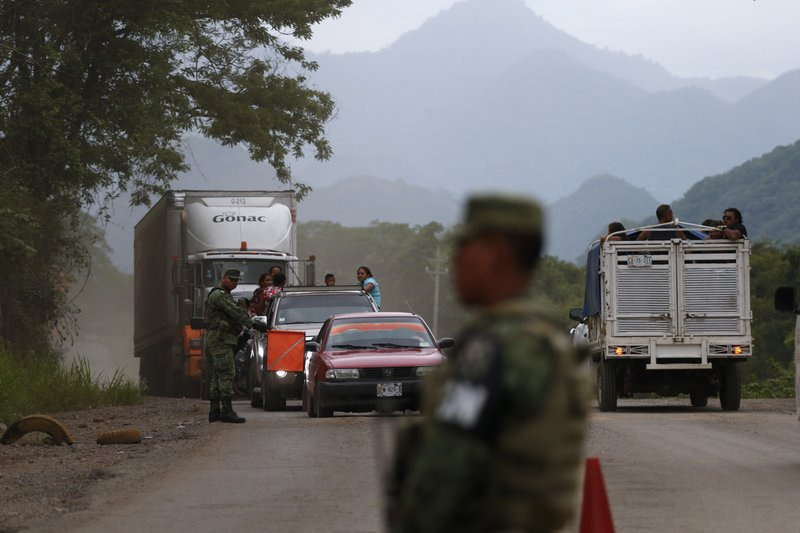 Soldiers wearing armbands for Mexico's National Guard man a temporary immigration checkpoint where officials were look for migrants, just north of Ciudad Cuauhtemoc, Chiapas State, Mexico, Saturday, June 15, 2019. Under pressure from the U.S. to slow the flow of migrants north, Mexico plans to deploy thousands of National Guard troops by Tuesday to its southern border region.(AP Photo/Rebecca Blackwell)
