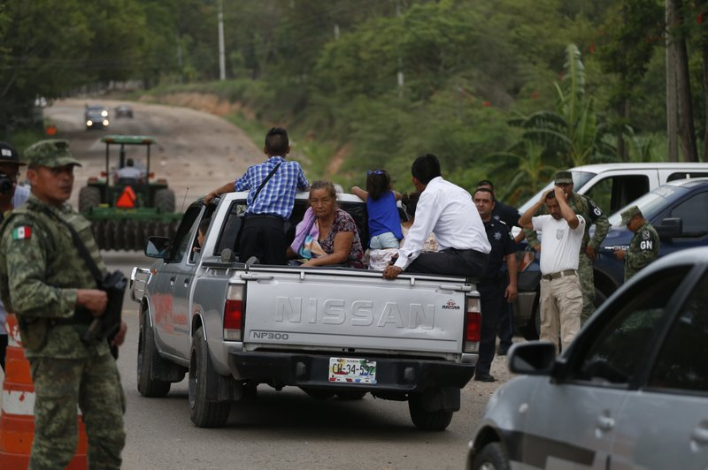 People ride in the back of a pickup as they pass through a temporary immigration checkpoint manned by soldiers wearing armbands for Mexico's National Guard, just north of Ciudad Cuauhtemoc, Chiapas State, Mexico, Saturday, June 15, 2019. Under pressure from the U.S. to slow the flow of migrants north, Mexico plans to deploy thousands of National Guard troops by Tuesday to its southern border region.(AP Photo/Rebecca Blackwell)