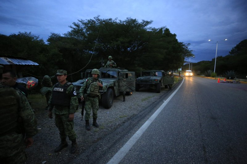 Soldiers wearing the armbands of Mexico's National Guard man a migration checkpoint north of Comitan, Chiapas State, Mexico, Saturday, June 15, 2019. Under pressure from the U.S. to slow the flow of migrants north, Mexico plans to deploy thousands of National Guard troops by Tuesday to its southern border region.(AP Photo/Rebecca Blackwell)