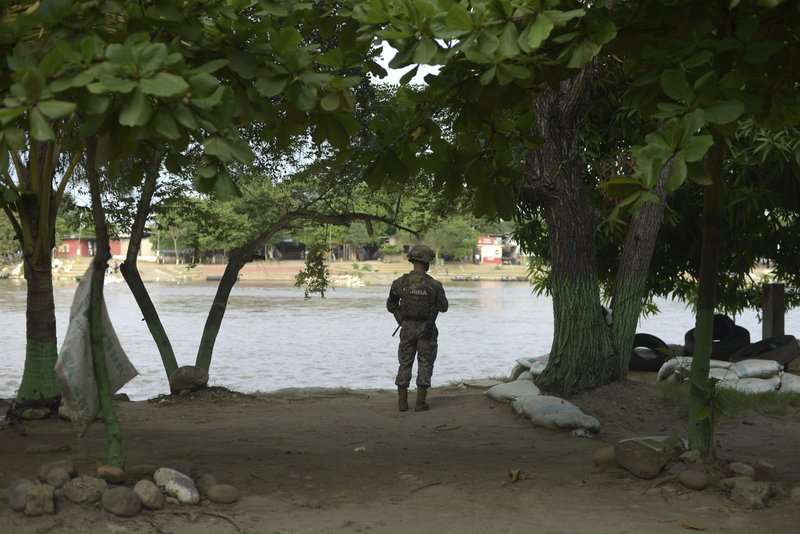 A Mexican marine stands guard on the Suchiate River, watching for migrants crossing from Guatemala to Ciudad Hidalgo, Mexico, Sunday, June 16, 2019. Mexico faces heightened pressure from the U.S. to reduce the surge of mostly Central American migrants through its territory. (AP Photo/Idalia Rie)