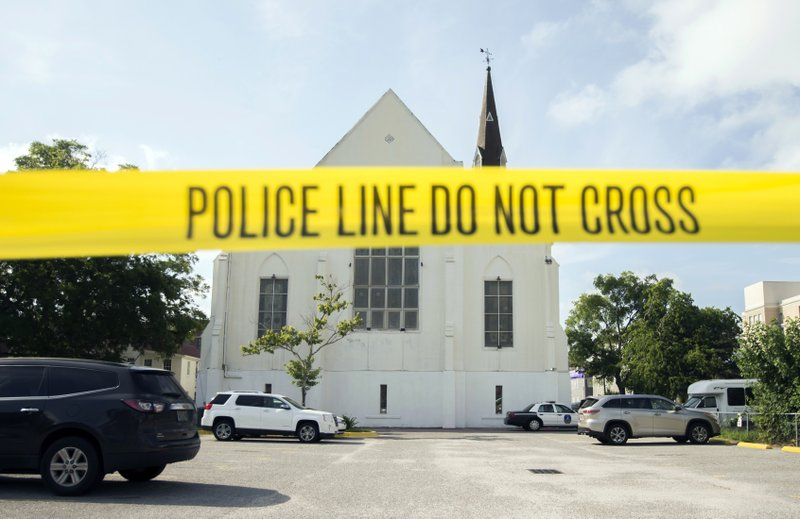 "FILE - In this June 19, 2015 file photo, police tape surrounds the parking lot behind the AME Emanuel Church as FBI forensic experts work the crime scene, in Charleston, S.C. he new documentary, ""Emanuel,"" explores life after the tragic shooting took place on June 17, 2015, as family members, friends and the community try to heal through faith and forgiveness. (AP Photo/Stephen B. Morton, File)"