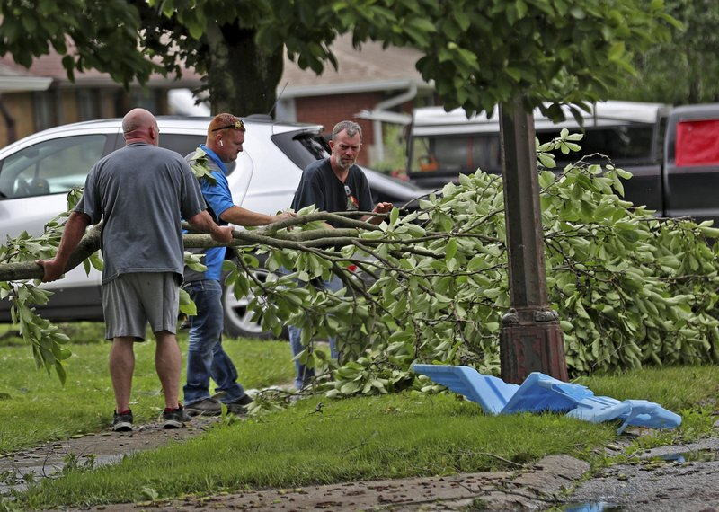 This Sunday, June 16, 2019, photo people clean up in Beech Grove, Ind., after a tornado moved through the area. Weather officials say severe storms in central Indiana caused floods and produced several tornadoes. (Kelly Wilkinson/The Indianapolis Star via AP)