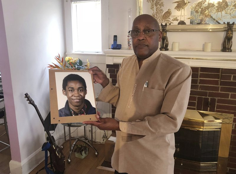 FILE - In this Sept. 5, 2018 file photo, Dia Khafra, father of Askia Khafra, holds a photo of his son in his Silver Springs, Md., home. A wealthy stock trader was sentenced Monday, June 17, 2019 to nine years in prison for his conviction in the fiery death of a man who was helping him secretly dig tunnels for a nuclear bunker beneath a Maryland home. Daniel Beckwitt, 28, apologized to the parents of 21-year-old Askia Khafra, who was burned beyond recognition by the September 2017 fire that broke out above the tunnels they were digging in a suburb of Washington, D.C. (AP Photo/Michael Kunzelman, file)