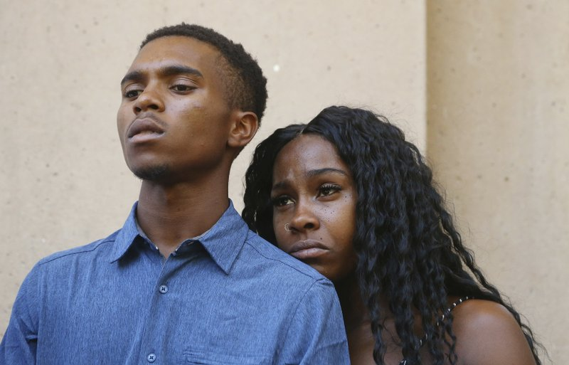 Dravon Ames, left, and Iesha Harper pause as they listen to a question during a news conference at Phoenix City Hall, Monday, June 17, 2019, in Phoenix. Ames and his pregnant fiancée, Harper, who had guns aimed at them by Phoenix police during a response to a shoplifting report say they don't accept the apologies of the city's police chief and mayor and want the officers involved to be fired.(AP Photo/Ross D. Franklin)