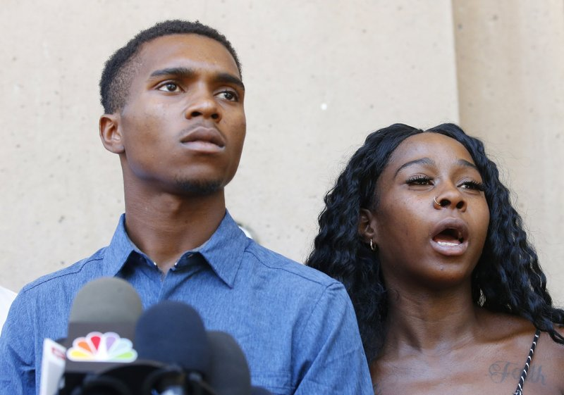 Iesha Harper, right, answers a question during a news conference as she is joined by her fiancee Dravon Ames, left, at Phoenix City Hall, Monday, June 17, 2019, in Phoenix. Ames and his pregnant fiancée, Harper, who had guns aimed at them by Phoenix police during a response to a shoplifting report say they don't accept the apologies of the city's police chief and mayor and want the officers involved to be fired.(AP Photo/Ross D. Franklin)