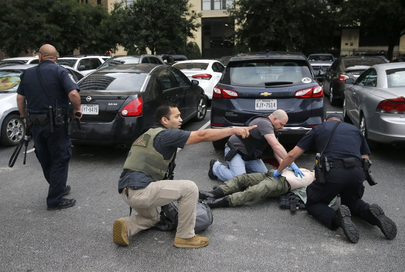 Members of the Department of Homeland Security and the U.S. Marshal's Service tend to the downed shooter after shots were fired Monday morning, June 17, 2019 at the Earle Cabell federal courthouse in Dallas. Law enforcement returned fire and the shooter was hit by gunfire and was pronounced dead at a hospital following the shooting. No officers or citizens were injured. (Tom Fox/The Dallas Morning News via AP)