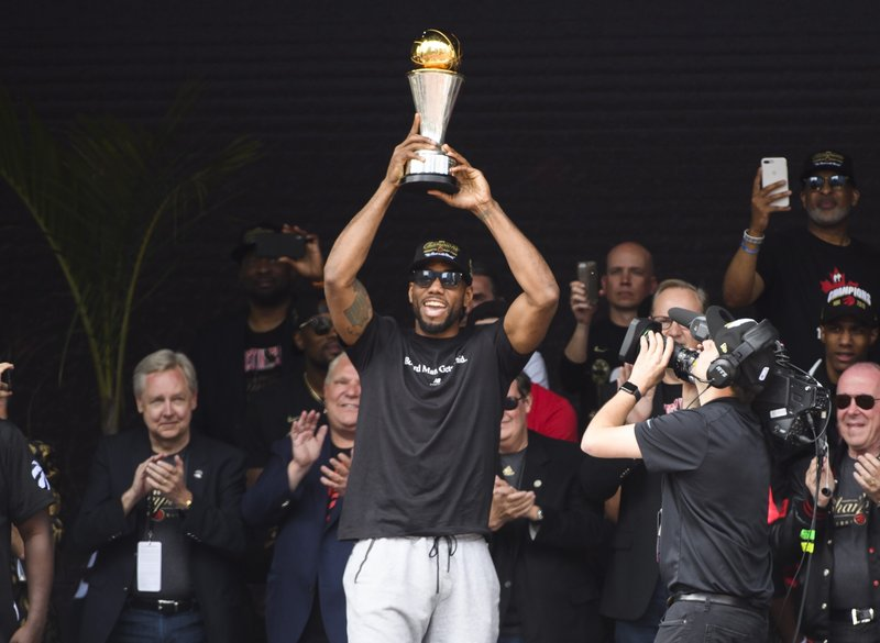 Toronto Raptors forward Kawhi Leonard hoists the MVP trophy next to teammates during the team's NBA basketball championship parade in Toronto, Monday, June 17, 2019. (Nathan Denette/The Canadian Press via AP)
