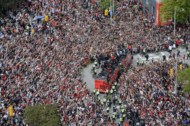 Fans cheer during the Toronto Raptors NBA basketball championship victory parade in Toronto, Monday, June 17, 2019. (Andrew Lahodynskyj/The Canadian Press via AP)