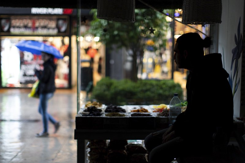 A pedestrian with an umbrella walks past a health food store which is still without electricity, in Buenos Aires, Argentina, Monday, June 17, 2019. As lights turned back on across Argentina, Uruguay and Paraguay after a massive blackout that hit tens of millions people, authorities were still largely in the dark about what caused the collapse of the interconnected grid and were tallying the damage from the unforeseen disaster. (AP Photo/Tomas F. Cuesta)