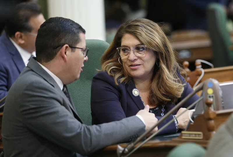 In this photo taken Thursday June, 13, 2019 Democratic Assembly members Rudy Salas Jr., of Bakersfield, left, and Sharon Quirk-Silva, of Fullerton, confer during the Assembly session in Sacramento, Calif. Both lawmakers broke from the rest of the Assembly Democratic caucus to vote against a measure to raise fees on phones to pay for an upgrade to the 911 system, Monday, June 17, 2019. The Assembly approved the bill.(AP Photo/Rich Pedroncelli)