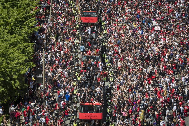 Members of the Toronto Raptors NBA basketball championship team ride on buses during a victory parade in Toronto, Monday, June 17, 2019. (Tijana Martin/The Canadian Press via AP)