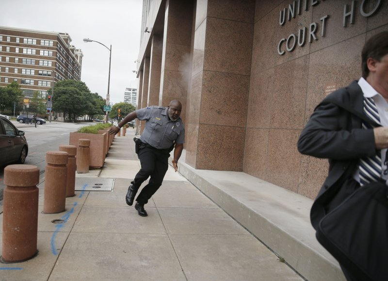 A security guard and a civilian run for cover as bullets ricochet off the building as a shooter (far background left) fires towards them on Monday, June 17, 2019 at the Earle Cabell federal courthouse in Dallas. A masked gunman opened fire Monday at the federal courthouse before being fatally shot in an exchange of gunfire with federal officers, witnesses and authorities said. No officers or citizens were injured. (Tom Fox/The Dallas Morning News via AP)