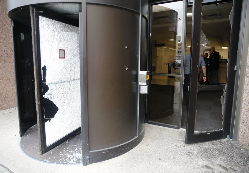 Shattered glass in the entry doors after shots were fired Monday, June 17, 2019 at the Earle Cabell federal courthouse in Dallas. A masked gunman opened fire Monday at the federal courthouse before being fatally shot in an exchange of gunfire with federal officers, witnesses and authorities said. No officers or citizens were injured. (Tom Fox/The Dallas Morning News via AP)