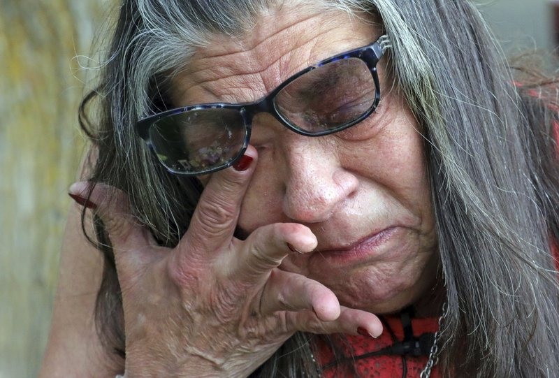 Melany Zoumadakis wipes a tear while visiting the grave of her daughter, Tanna Jo Fillmore, on Friday, April 26, 2019, in Salt Lake City. More than two years after her daughter's suicide, her mother says she still grieves and thinks about her constantly. Fillmore told her mother she desperately needed her prescription medicines, but a jail nurse wouldn't provide them. Her mother has filed sued. (AP Photo/Rick Bowmer)