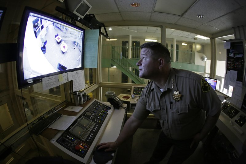 Sheriff Brian Martin looks at a video monitor in a control area of the Lake County Jail in Lakeport, Calif., on Tuesday, April 16, 2019. The sheriff instituted many reforms and changes, including a larger video surveillance monitor, following the 2015 suicide of a woman who had repeatedly cried for help. Her son's wrongful death suit resulted in a $2 million settlement. (AP Photo/Eric Risberg)