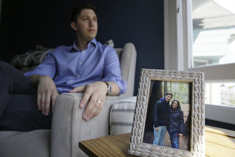 Dane Shikman sits by a photograph showing him with mother, Elizabeth Gaunt, at his home in San Francisco on Friday, April 19, 2019. Shikman's mother killed herself in 2015 at the Lake County, Calif., jail, after she was picked up for acting erratically. Gaunt, who had a history of mental health and substance abuse problems, had repeatedly screamed for help and pleaded to see a doctor. Her son's wrongful death lawsuit resulted in a $2 million county settlement. (AP Photo/Eric Risberg)