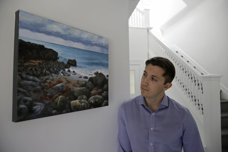 Dane Shikman stands by a photo showing where the ashes of his mother, Elizabeth Gaunt, were scattered in Ireland, while at his home in San Francisco on April 19, 2019. Shikman's mother, a former social worker with mental health and substance abuse problems, killed herself in 2015 at the Lake County, Calif, jail, after pleading to see a doctor and repeatedly begging for help.  Her son's wrongful death t resulted in a $2 million county settlement. (AP Photo/Eric Risberg)