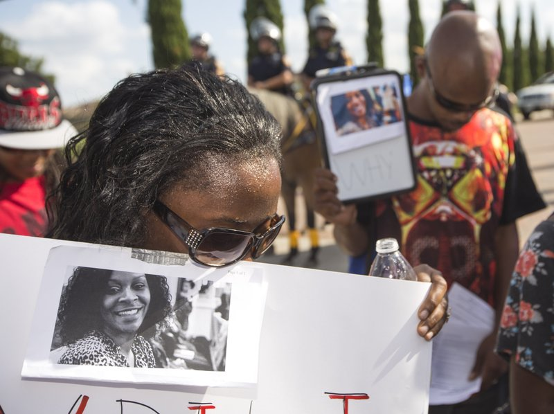 FILE - In this Sunday, July 26, 2015 file photo, Margaret Hilaire bows her head in prayer during a demonstration calling for the firing and indictment of Texas State Trooper Brian Encinia in Katy, Texas. Sandra Bland was found dead in her cell on July 13 in the Waller County Jail, just days after being arrested by Encinia during a traffic stop. Authorities determined through an autopsy that Bland hanged herself with a plastic bag. (Brett Coomer/Houston Chronicle via AP)
