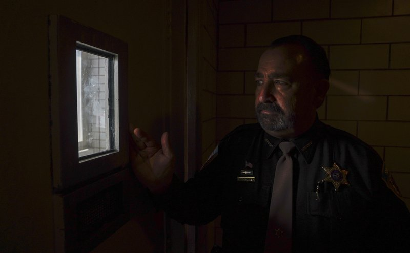 Dane County, Wis., Sheriff David Mahoney looks through a small window in a solitary confinement cell at the county jail in Madison. Mahoney says he has no separate housing for inmates with certain behavioral, medical or mental health problems, so he has to put them in these cells even though he says it's