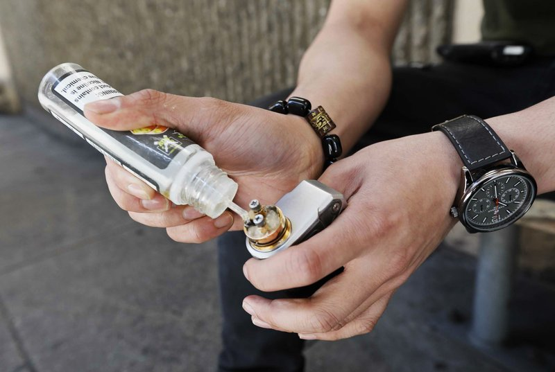 In this Monday, June 17, 2019, photo, Jacky Chan, 23, refills his electronic cigarette with vaping liquid in San Francisco. San Francisco supervisors are considering whether to move the city toward becoming the first in the United States to ban all sales of electronic cigarettes in an effort to crack down on youth vaping. The plan would ban the sale and distribution of e-cigarettes, as well as prohibit e-cigarette manufacturing on city property. (AP Photo/Samantha Maldonado)