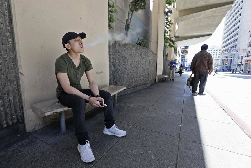 In this Monday, June 17, 2019, photo, Jacky Chan, 23, takes a vaping break from his job at a smoke shop in San Francisco. San Francisco supervisors are considering whether to move the city toward becoming the first in the United States to ban all sales of electronic cigarettes in an effort to crack down on youth vaping. The plan would ban the sale and distribution of e-cigarettes, as well as prohibit e-cigarette manufacturing on city property. (AP Photo/Samantha Maldonado)