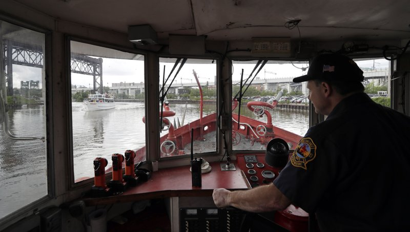 Firefighter Greg Geracioti maneuvers the Anthony J. Celebrezze down the Cuyahoga River, Thursday, June 13, 2019, in Cleveland. The fire boat extinguished hot spots on a railroad bridge torched by burning fluids and debris on the Cuyahoga River in 1969. (AP Photo/Tony Dejak)