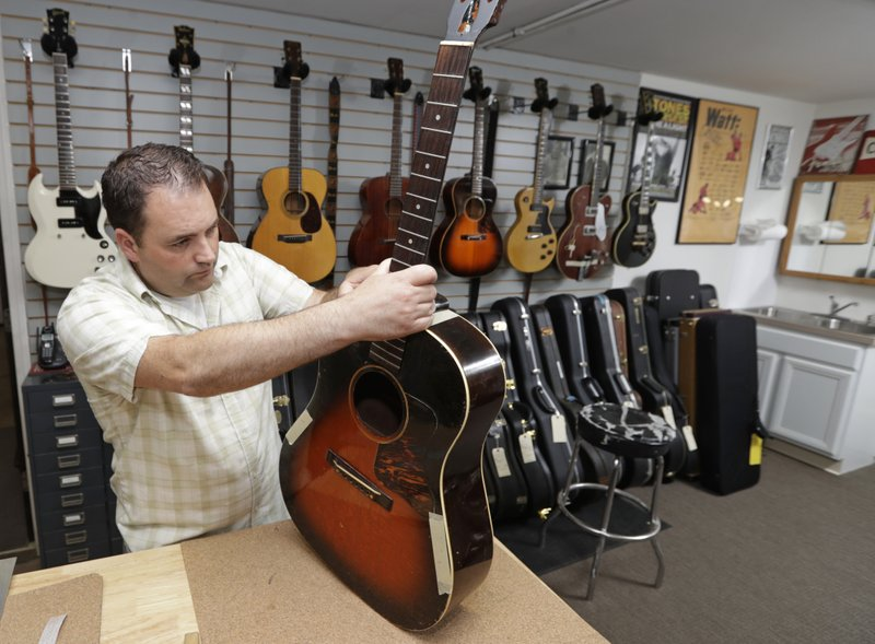 Jacob Tuel, owner of Burning River Guitars, repairs the neck of a guitar, Monday, June 10, 2019, in Akron, Ohio. Tuel named his guitar shop after the 1969 blaze on the Cuyahoga River, in Cleveland. (AP Photo/Tony Dejak)